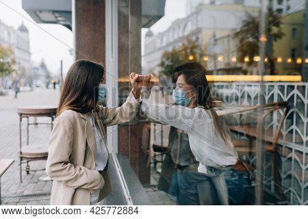 Two Women In Protective Masks Opposite Each Other, Window Between Them.