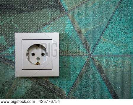 Close-up Of A Gray Electrical Socket On The Wall With An Abstract Pattern.