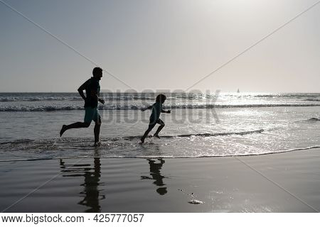 Father And Son Running On Beach. Daddy With Kid Boy In Sea Or Ocean. Weekend Family Day.
