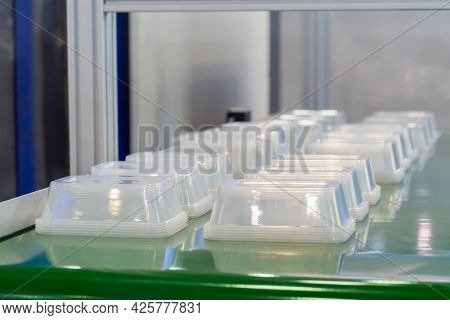 Stack Of Polypropylene Food Containers On Conveyor Belt Of Automatic Plastic Injection Molding Machi