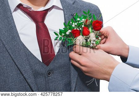 The Hands Of The Witness' Boyfriend At The Wedding Attach The Boutonniere To The Groom's Suit Close-