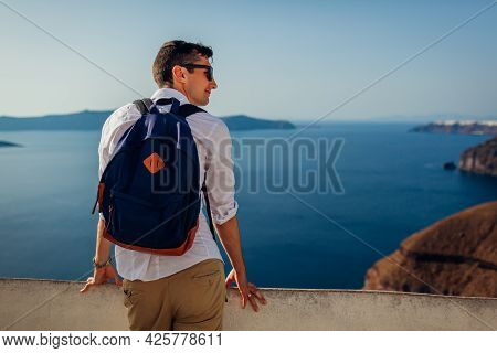 Santorini Traveler Man Relaxing Enjoying Caldera Landscape View In Fira, Greece. Tourism, Traveling,