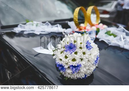 Wedding Bouquet Of White And Blue Flowers Lies On The Bonnet Of The Car Against The Background Of Ri