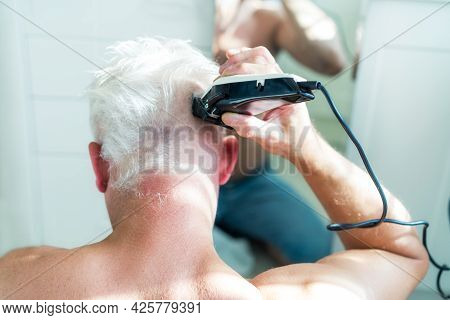 Back View White Hair Man Doing Self Haircut With A Clipper And Looks In The Mirror. Self-care At Hom