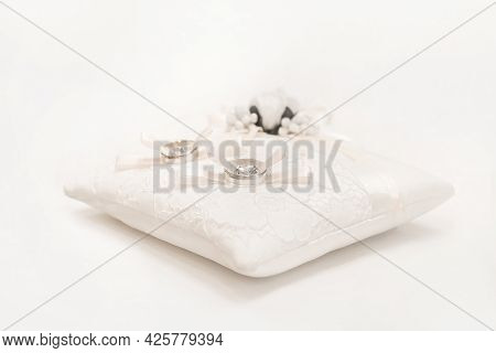 Wedding Rings Of The Bride And Groom On A White Decorative Pillow On The Table In The Registry Offic