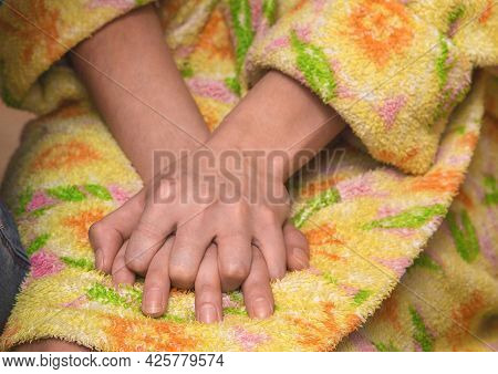 The Girl In The Robe Squeezes Her Hands Together. Excitement, Nerves And Anxiety Concept.