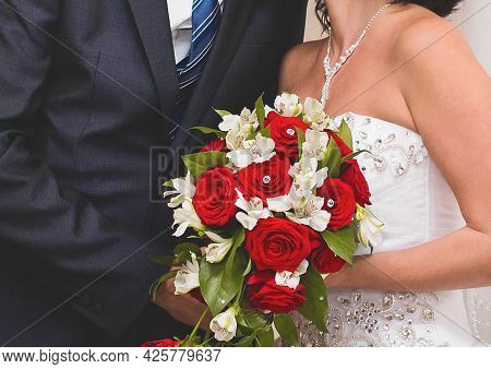Bride And Groom In A White Wedding Dress Holds A Bouquet Of Beautiful Flowers Of White And Red Roses