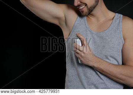 Man Applying Deodorant On Black Background, Closeup. Space For Text