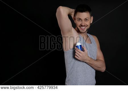 Handsome Man Applying Deodorant On Black Background. Space For Text