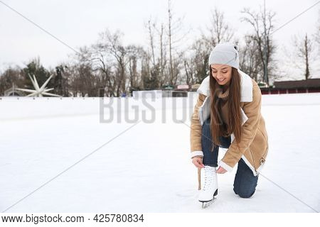 Woman Lacing Figure Skate On Ice Rink. Space For Text