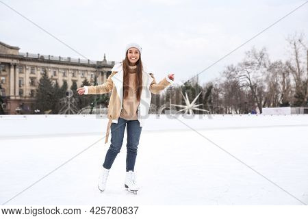Happy Woman Skating Along Ice Rink Outdoors. Space For Text