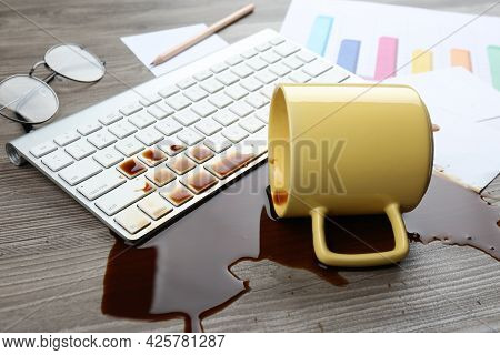 Cup Of Coffee Spilled Over Computer Keyboard On Wooden Office Desk