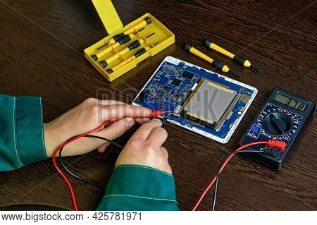 The Engineer Measures The Voltage On The Electrical Board. Repair Of Electrical Equipment. An Electr