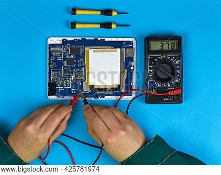Technician Or Engineer Repairs The Digital Board And Performs A Multimeter Test. Top View On A Blue