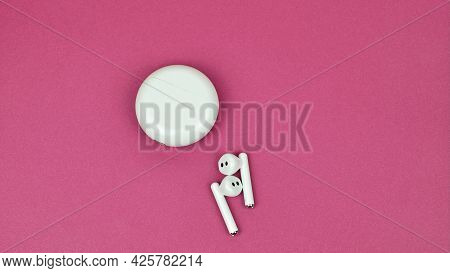 Wireless Earphone On A Pink Background, Copy Space. White Case And Wireless Headphones. Round White
