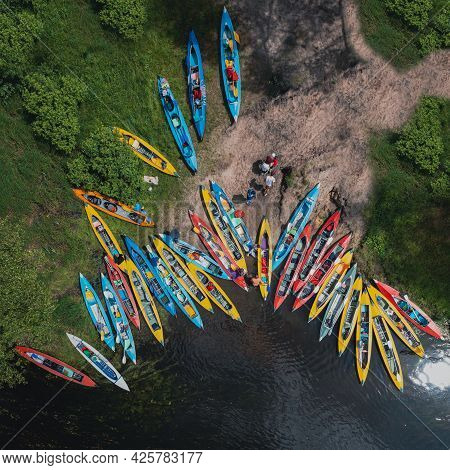 Camp And Pier Of Tourist Kayaks - Top View Shot Over The River Bank - Camp During Kayaking On The Ri