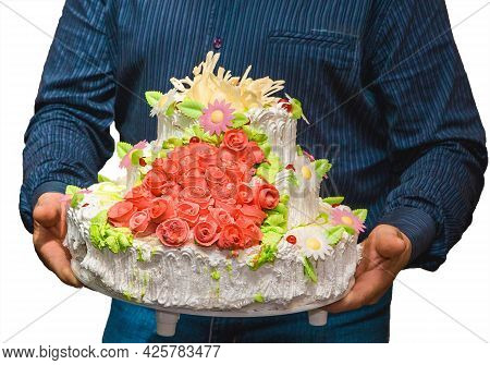 A Man Carries A Large Tiered White Cream Wedding Cake With Red Sedous Sweet Roses Decorated Against