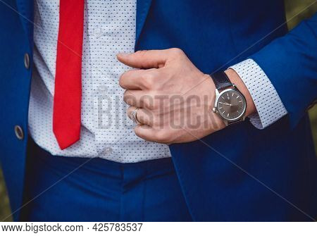 The Hand Of A Man With A Hand Watch Holds On To A Blue Suit Against The Background Of A White Shirt