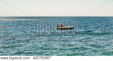A Faulty Rubber Boat With A Motor, A Man Turns On The Motor, A Summer Day On A Calm Sea.