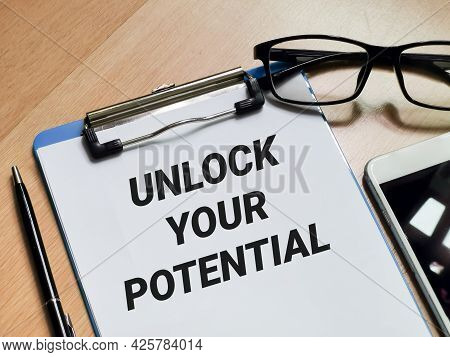 Business And Technology Concept. Phrase Unlock Your Potential Written On Paper Clipboard With Pen,sm