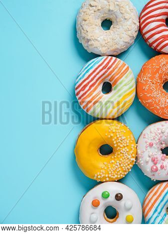 Delicious Glazed Donuts On Blue Background. Vertical Flat Lay - Set Of Different Colorful Donuts Or