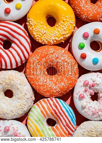 Assorted Colorful Glazed Donuts With Sprinkle. Creative Layout Made From Delicious Glazed Donuts. Ve