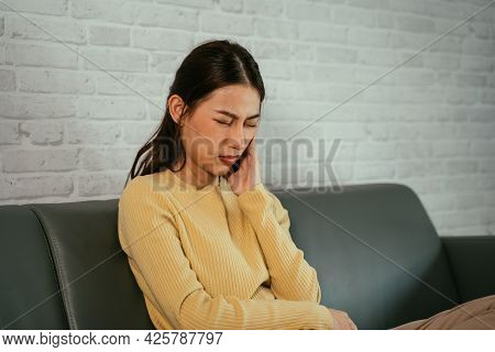 Asian Woman Sitting On Couch With Folded Legs And Closed Eyes Pressing Cheek As Suffering From Tooth