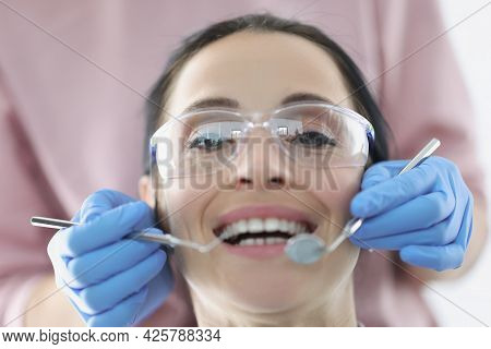 Dentist Examining Oral Cavity Of Female Patient Wearing Safety Glasses In Clinic