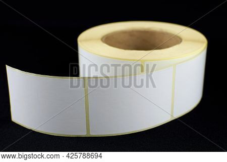 Babina Of Self-adhesive Stickers On A Black Background. Self-adhesive White Label Roller For Printin