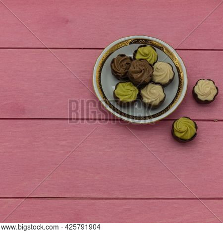 On A White Porcelain Saucer With A Gold Border, There Are Chocolates With Pistachio And Cream Fillin