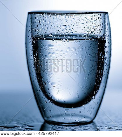 glass of purity water with water drops  on blue background