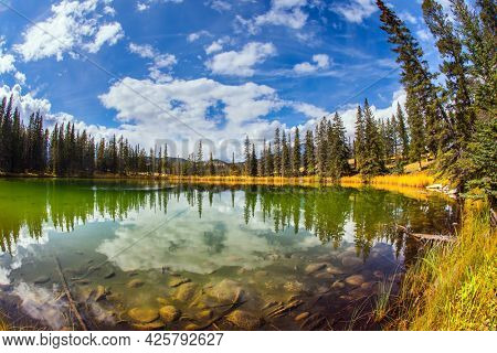 The Rocky Mountains. Round small lake with cold green water. Canada. Jasper Park in Indian summer. Coniferous forest reflected in water. Travel and photo tourism concept