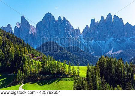 Magnificent Dolomites on a sunny autumn day. Green meadows in the Val de Funes. Europe, Val de Funes. Tyrol, Italy