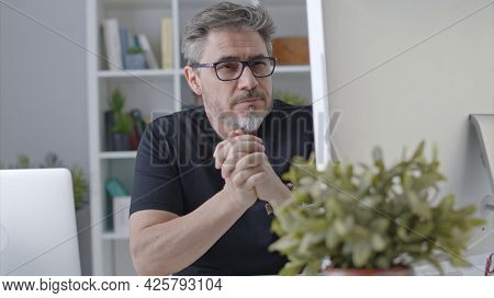 Older white man in glasses sitting at desk using desktop computer in home office. 50s businessman staying home in casual working online thinking on business solution.