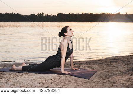 A Woman Practices Yoga On The River Bank At The Beach At Sunset. Cobra Pose, Upward Facing Dog Asana