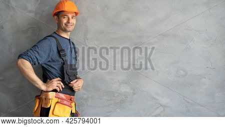 Smiling Construction Worker Worker Stands In Front Of A Gray Concrete Wall Wearing An Orange Hard Ha