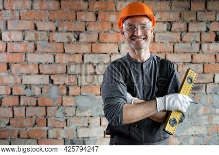 Portrait Of A Smiling Professional Repairman Standing Near The Wall With A Building Level In His Han