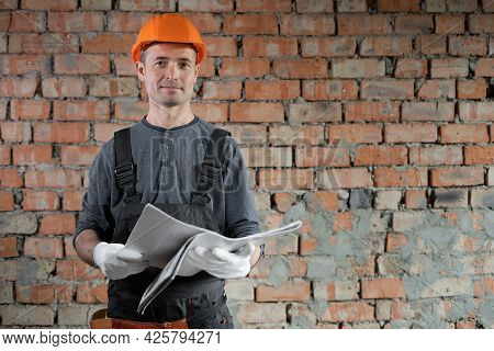 Construction Worker Engineer With Hard Hat With Red Brick House Renovation Construction Site Plan On