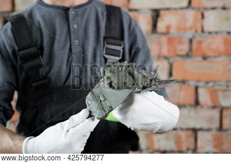 Close-up Of Spatulas Or Trowels With Cement Or Plaster On Them In The Hands Of The Foreman. A Builde
