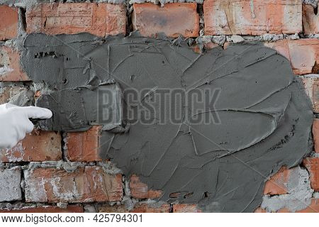 Close-up Of Cement Plastering Brick Wall In A House. A Gloved Hand Of A Builder Applies Plaster To A