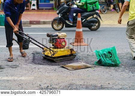 Road Repair, Workers And Machinery Are Working Paved Road With Asphalt And Gravel, Street Constructi