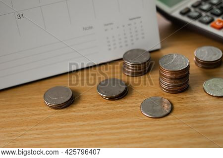 Stack Thai Coin With Calculator And Calendar On Wood Background. Planing Earn Investment And Saving