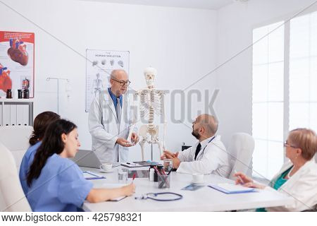 Therapist Senior Man Discussing Bone Structure Analyzing Anatomy Body Skeleton Presenting Medical Ex