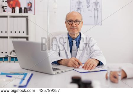 Portrait Of Senior Man Specialist Physician Looking Into Camera Sitting At Desk In Meeting Room Work