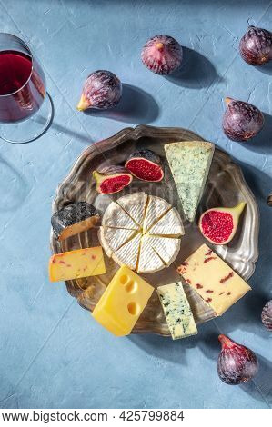 Cheese Platter With Fruit And A Glass Of Red Wine, Shot From The Top On A Blue Background. Brie, Blu