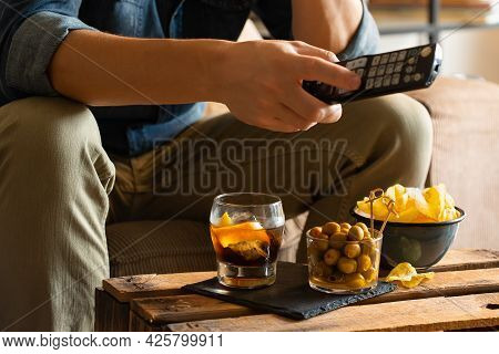 Man Drinking Vermouth And Eating Snacks After Work At Home