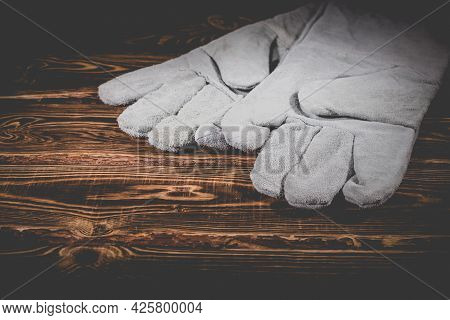 White Leather Welder Gloves On A Wooden Background. A Studio Photo With Hard Lighting.