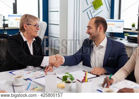 Consultant Greeting International Client With Handshake After Planning Partnership Deal. Executive D
