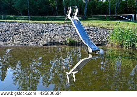 Childs Slide Mirroring In Calm Water At Beach