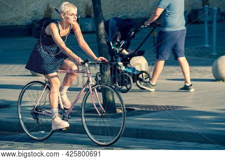 Vilnius, Lithuania - June 30 2021: Beautiful Blonde Short Hair Girl With Short Dress And Tattoos Wit